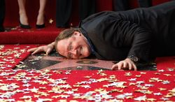 "Pixar Chief Creative Officer John Lasseter embraces his star on the Hollywood Walk of Fame on Tuesday. The ""Cars 2"" director received the 2,453rd star. (Associated Press)"