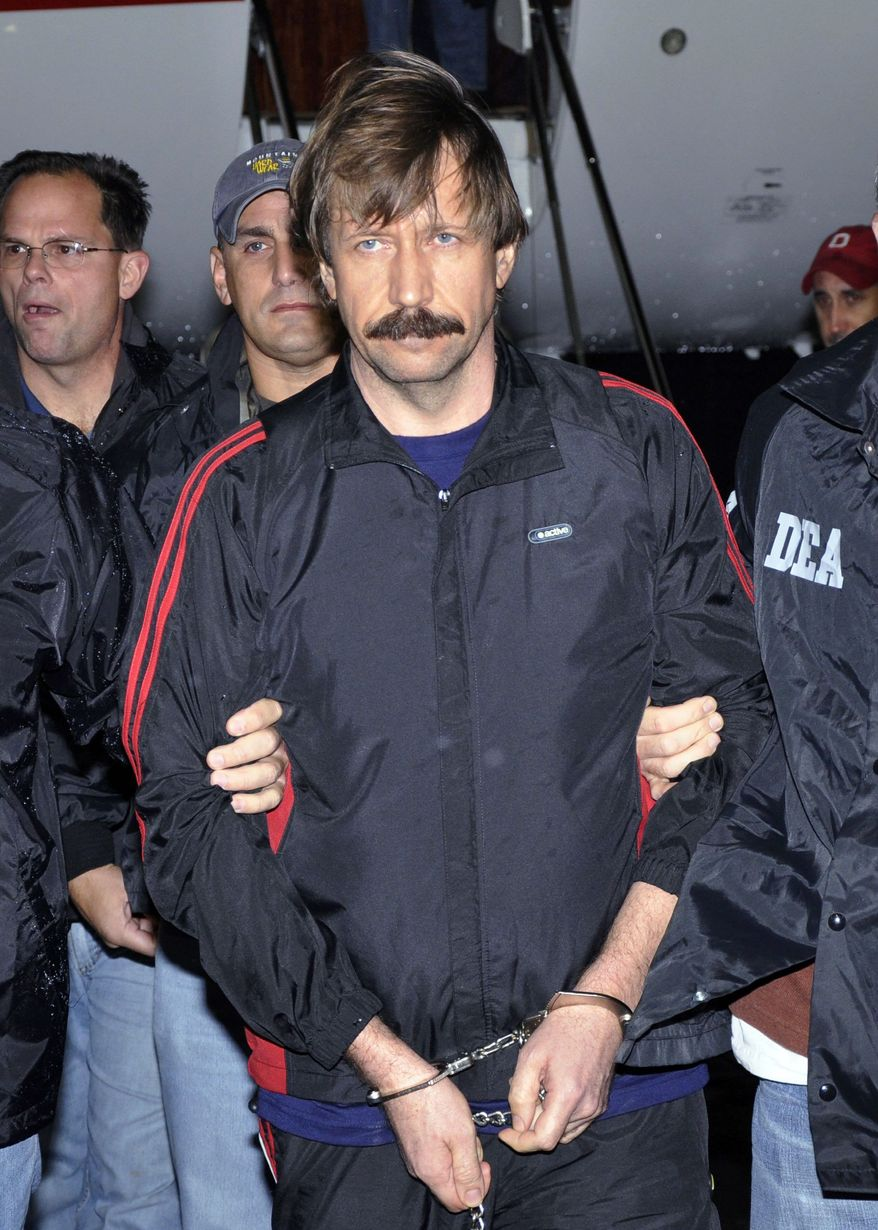 Viktor Bout is escorted off a flight from Bangkok to New York last November during his extradition to face trial on charges of transporting weapons. A jury found him guilty on all counts Wednesday. (Associated Press)