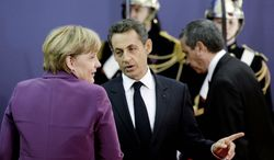 French President Nicolas Sarkozy speaks with German Chancellor Angela Merkel during arrivals for the G-20 economic summit in Cannes, France, on Wednesday. (Associated Press)
