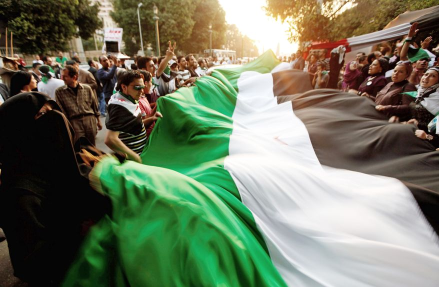 Protesters unfurl a large Syrian flag in front of the Arab League headquarters in Cairo on Wednesday as more than 100 people protesting the rule of Syrian President Bashar Assad gathered outside the building where foreign ministers were meeting. (Associated Press)