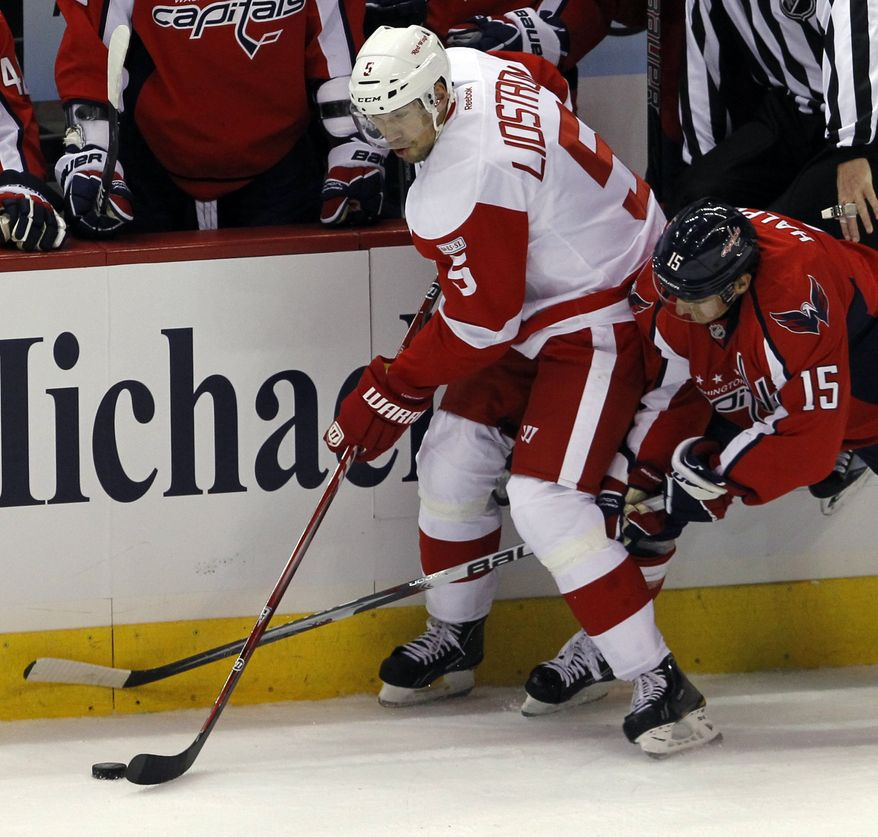 Detroit Red Wings defenseman Nicklas Lidstrom (5) of Sweden controls the puck past Washington Capitals center Jeff Halpern (15) during the first period of an NHL hockey game Saturday, Oct. 22, 2011, in Washington. (AP Photo/Ann Heisenfelt)