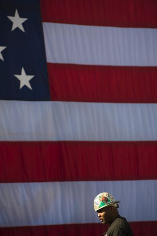 Tyrone Thomas of Suitland, Md, and member of Ironworkers Local 5 walks past the U.S. flag as he and others wait for President Barack Obama's arrival and remarks urging Congress to pass the infrastructure part of the American Jobs Act, in front of a crowd which included iron workers and steam fitters, at Georgetown Waterfront Park in Washington, D.C., Wednesday, Nov. 2, 2011. (Photo/Rod Lamkey Jr./The Washington Times)