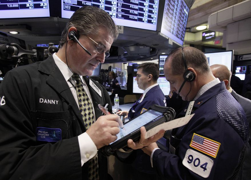 Daniel Kryger (left) works with fellow traders on the floor of the New York Stock Exchange on Wednesday, Nov. 2, 2011. (AP Photo/Richard Drew)