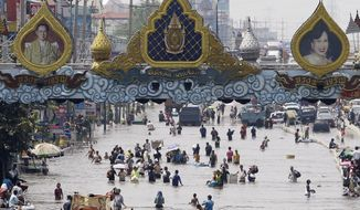 Residents wade through a flooded street beneath portraits of Thailand's King Bhumibol Adulyadej and Queen Sirikit in the Rangsit district on the outskirts of Bangkok. Water has been a virtual obsession for the king for the past four decades. Flooding this year is the worst it's been in 50 years. (Associated Press)