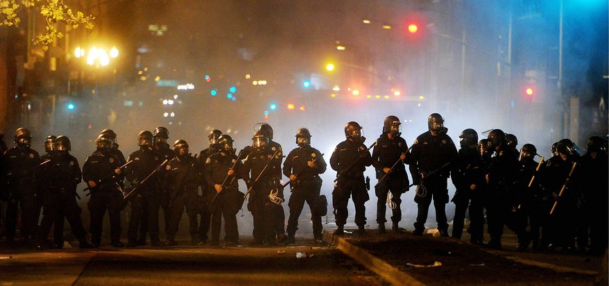 Riot police advance on Occupy Oakland protesters early Thursday in the port city. After a peaceful day-long protest by thousands of demonstrators, several hundred clashed with police trying to stop them from spraying graffiti, breaking windows and setting fire to garbage. (Associated Press)