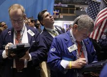 Traders Dennis Maguire (left) and Richard Newman (right) work on the floor of the New York Stock Exchange on Nov. 3, 2011. (Associated Press)