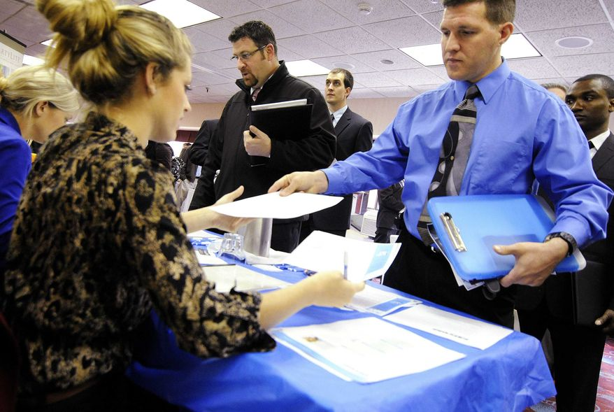 In this Nov. 2, 2011, photo, Clarence Turner of Little Canada, Minn., hands in his resume at the Minneapolis Career Fair held in Bloomington, Minn., where he was looking for a hotel audit job. (AP Photo/Jim Mone)