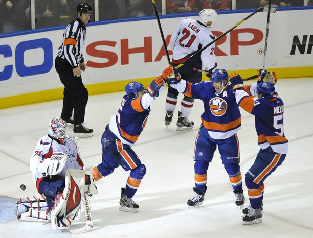 Washington Capitals goalie Tomas Vokoun reacts as New York Islanders' P.A. Parenteau, Brian Rolston  and Frans Nielsen celebrate what ended up being the game-winnin