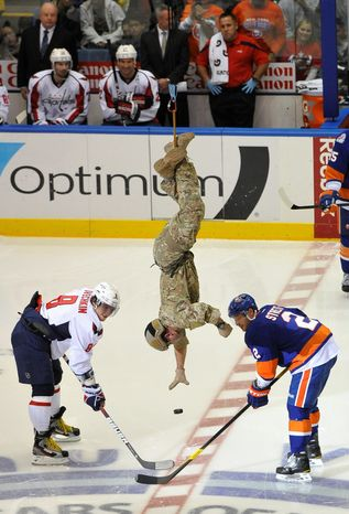 Air National Guard Staff Sgt. Matthew Zimmerman drops the ceremonial first puck Saturday between Capitals left wing Alex Ovechkin (left) and Islanders defenseman Mark Streit. The Capitals went on to suffer their third loss of the season as turnovers and poor goaltending plagued Washington. (Associated Press)