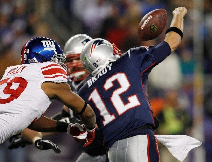 New York linebacker Michael Boley forces New England quarterback Tom Brady to fumble during the Giant' 24-20 victory in Foxborough, Mass. (Associated Press)