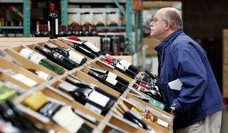 Pat Kenyon looks over the wine selection at a Costco warehouse store Oct. 31 in Seattle. Whether Costco will be able to sell hard liquor alongside the wine depends on the outcome of a Washington state referendum on Tuesday. (Associated Press)