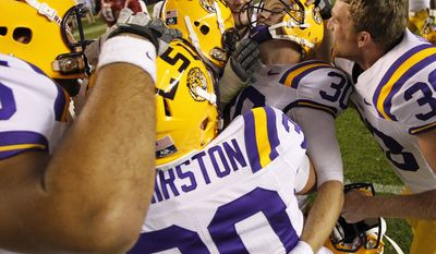 LSU kicker Drew Alleman is embraced by teammates after the second half of an NCAA college football game against Alabama, Saturday, Nov. 5, 2011, in Tuscaloosa, Ala. Alleman kicked the winning field goal as LSU won 9-6. (AP Photo/Dave Martin)