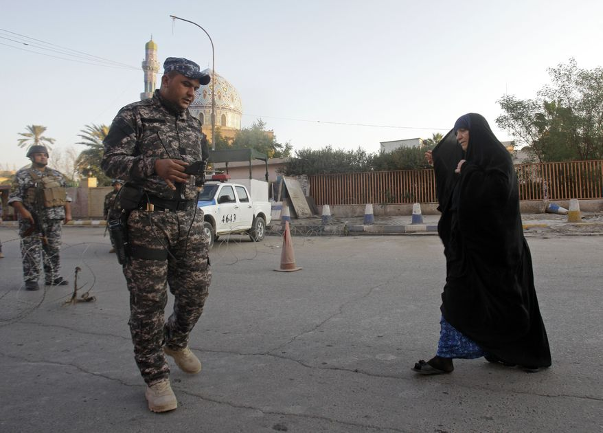 An Iraqi police officer uses a bomb detector to search a woman outside the 14th Ramadan Mosque (in the background) on the first day of Eid al-Adha in Baghdad on Sunday, Nov. 6, 2011. Eid al-Adha, or the Feast of the Sacrifice, commemorates the prophet Abraham's faith in being willing to sacrifice his son. (AP Photo/Khalid Mohammed)