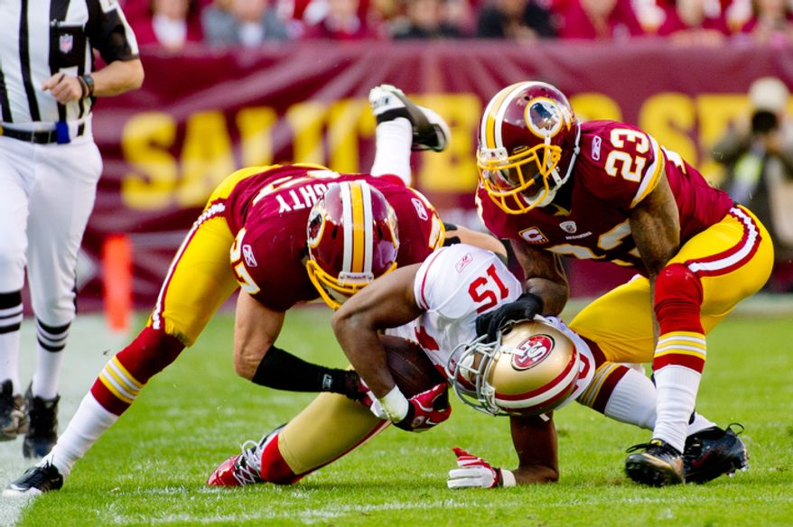 Washington Redskins Reed Doughty (37) and DeAngelo Hall (23) tackle San Francisco 49ers Michael Crabtree (15) after he picks up 21 yards during the first quarter. (Andrew Harnik / The Washington Times)