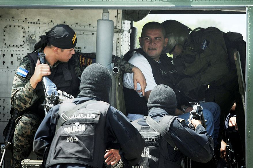 Alleged drug trafficker Mario Ponce Rodriguez from Guatemala is escorted by police and army personnel during his extradition to the U.S. from Tegucigalpa, Honduras, on Oct. 10. Almost half of the cocaine that reaches the United States is now offloaded somewhere along Honduras' coast and heavily forested interior. (Associated Press)
