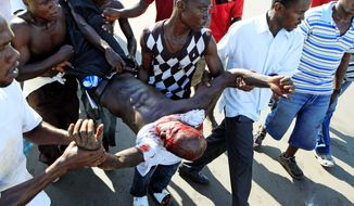 A wounded man is carried to emergency aid during a clash with Liberian police at opposition party headquarters in Monrovia on Monday. Violence broke out at the headquarters, and at least two people were killed, less than 24 hours before Liberia's presidential runoff, considered a test of the country's fragile peace after civil war. (Associated Press)