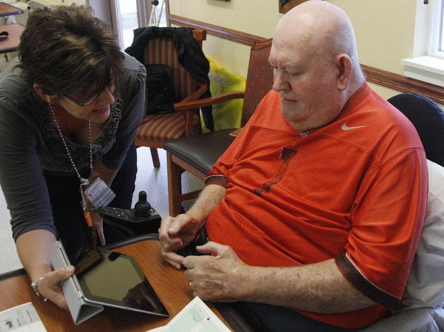 Lewis Crew, 75, who suffers from severe arthritis, gets help using an iPad from a member of a voter-assistance team in early voting Friday in Beaverton, Ore., in a special primary election to replace former Rep. David Wu, who resigned. (Associated Press)