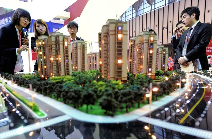 Sales promoters talk to visitors at a housing fair in Nanjing, China. With real estate prices through the roof, 70 to 80 percent of potential buyers are unable to purchase housing some of China's major cities. (Associated Press)