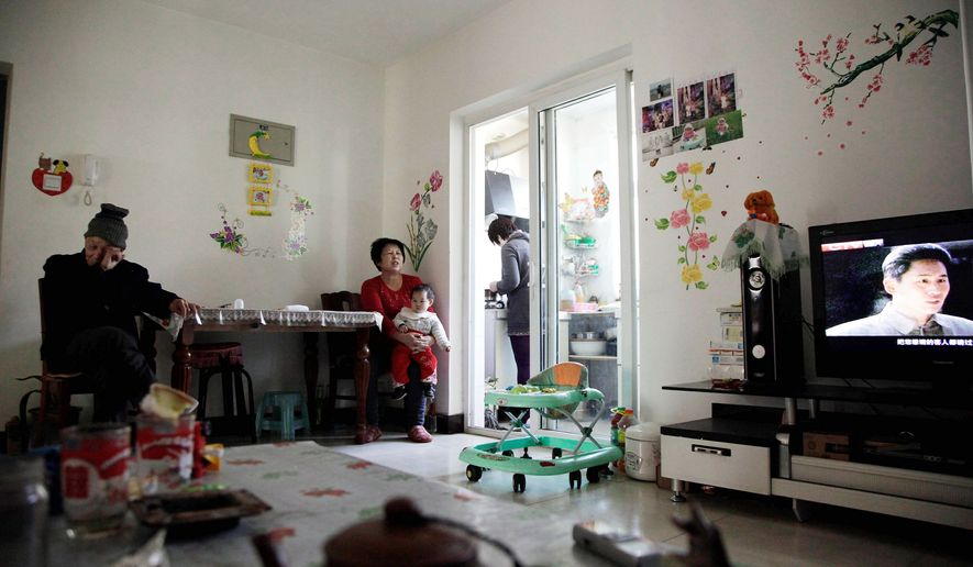 A family rests in its new apartment home after relocating from farmlands in northern China. While trying to protect farmland from development amid a housing boom, officials are going after the land under farmers' homes. (Associated Press)