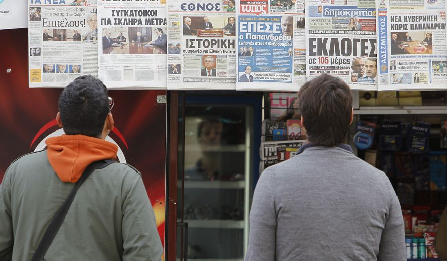 Two men read the front pages of the Greek daily newspapers at a kiosk in central Athens on Monday, Nov. 7, 2011. (AP Photo/Thanassis Stavrakis)