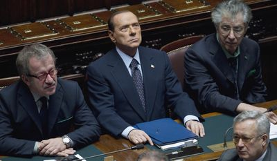 Italian Premier Silvio Berlusconi (center), flanked by Interior Minister Roberto Maroni (left) and Reforms Minister Umberto Bossi, attends a voting session in the Chamber of Deputies, Parliament's lower house, in Rome on Tuesday, Nov. 8, 2011. (AP Photo/Andrew Medichini)