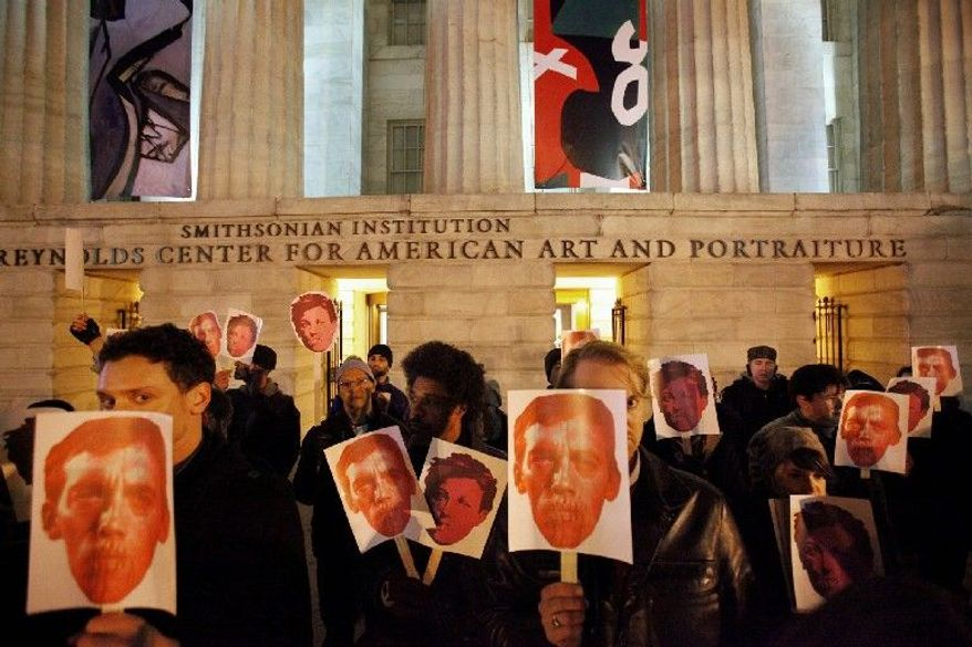 ** FILE ** In this Dec. 2, 2010, file photo, protesters hold masks in support of artist David Wojnarowicz on the steps of the Smithsonian's National Portrait Gallery, after a video by Wojnarowicz was removed from exhibition at the museum, in Washington. The Andy Warhol Foundation said Monday, Dec. 13, 2010, it will withhold future funding to the Smithsonian Institution unless a video removed from the gallery after a Catholic group complained is restored.(AP Photo/Jacquelyn Martin, File)