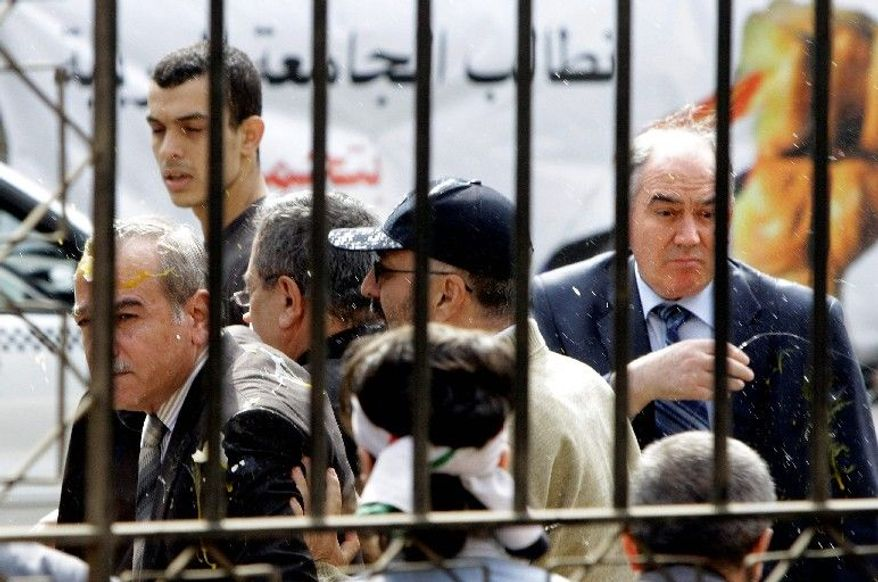 Syrian protesters throw eggs at Abdul-Aziz al-Khair (left), a member of the Syrian National Coordination Committee, and other opposition leaders as they try to enter Arab League headquarters in Cairo on Wednesday. They were supposed to hold talks with the organization's chief on violence in Syria. (Associated Press)