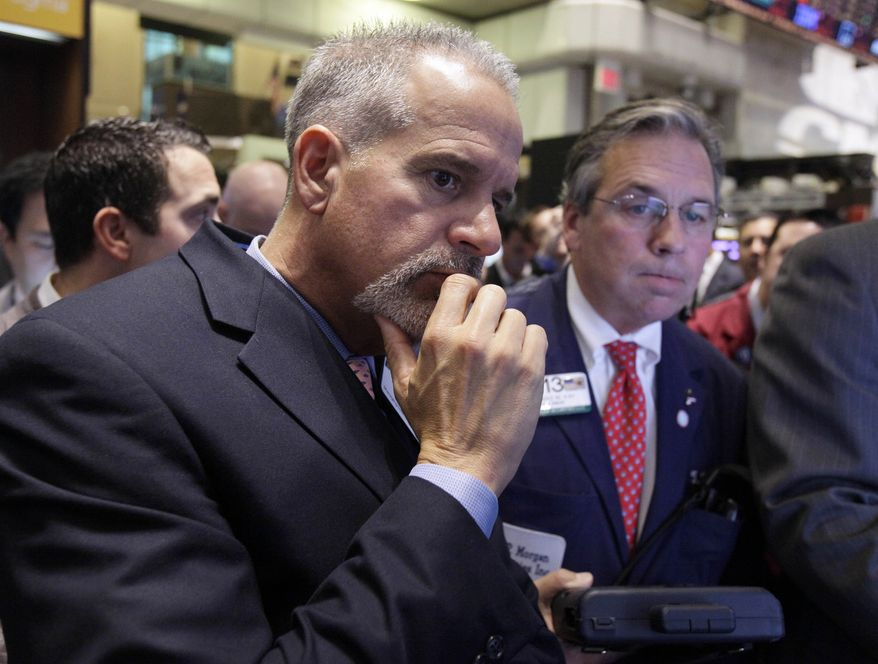 Floor official Rudi Maas (left) and trader Thomas Kay work on the floor of the New York Stock Exchange on Wednesday, Nov. 9, 2011. The Dow Jones industrial average was down sharply after Italy's borrowing costs soared. (AP Photo/Richard Drew)