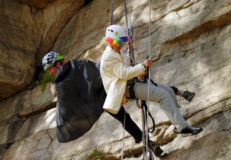 In this photo taken Oct. 28, 2011 and released by Ascent Services Worldwide LLC, climbers Silas Rossi, left, and Angela Hawse, in Halloween costumes, dangle beneath an overhang in the Guide's Olympics during the American Mountain Guides Association's annual conference at the Shawangunk climbing area in New Paltz, N.Y. (AP Photo/Ascent Services Worldwide LLC, Joe Lentini)