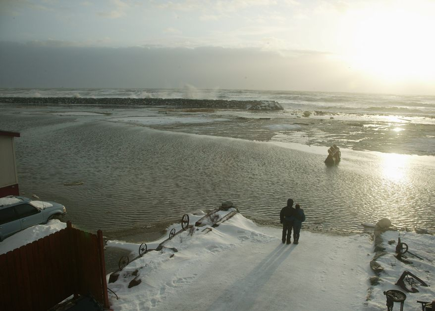 A couple stand in front of flooded River Street in Nome, Alaska, on Wednesday. High winds and surging waves pummeled Alaska's western coast, forcing residents of Nome and isolated native villages to seek higher ground inland. (Associated Press)