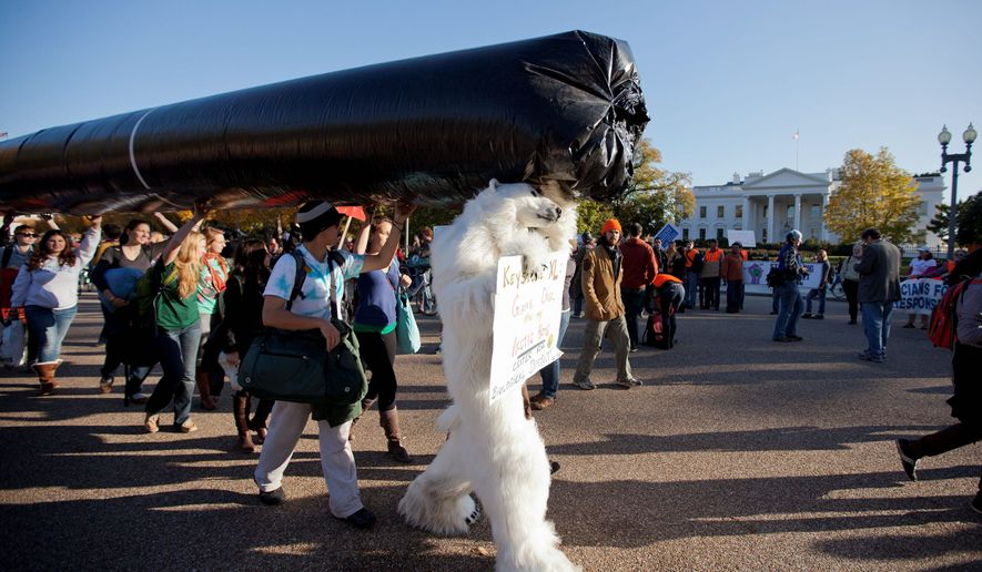 Demonstrators march with a replica pipeline outside the White House on Sunday to protest TransCanada's proposed Keystone XL pipeline. Citing environmental fears, the State Department on Thursday ordered a new review of the Canada-to-Texas pipeline. (Associated Press)