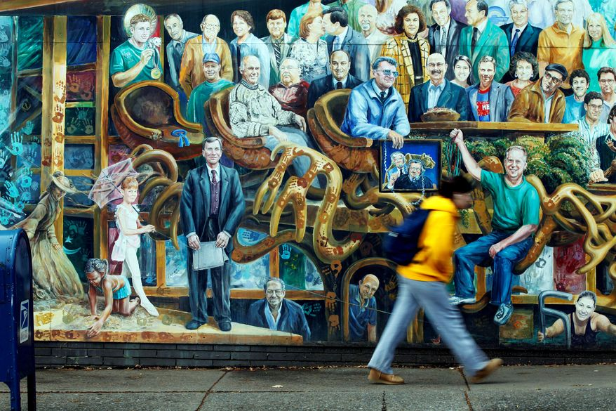 A mural in State College, Pa., has replaced the image of ex-Penn State defensive coordinator Jerry Sandusky, charged with 40 counts of child sex abuse, with an empty chair and blue ribbon (left). (Associated Press)