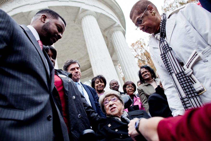 Alyce Dixon, who served at a military post office in France during World War II, speaks with Kwame R. Brown (left), chairman of the D.C. Council, and Eleanor Holmes Norton (right), the city's delegate to Congress, during a rededication ceremony Thursday at the District of Columbia War Memorial. (T.J. Kirkpatrick/The Washington Times)