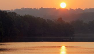 The sun rises over Oxon Cove Park and is reflected in a Potomac River estuary in Oxon Hill. Water quality in the Potomac was already bad and has grown worse in the past five years, a Potomac Conservancy report said Thursday. (Associated Press)