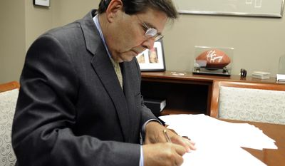 Jefferson County Commission President David Carrington signs the Chapter 9 bankruptcy papers in his office at the Jefferson County Courthouse in Birmingham, Ala., on Wednesday, Nov. 9, 2011. (AP Photo/The Birmingham News, Joe Songer)