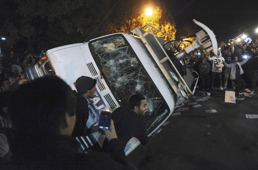 Penn State students flip a television news van during a riot after the announcement that Joe Paterno had been fired as head football coach on Wednesday, Nov. 9, 2011. (AP Photo/Pittsburgh Post-Gazette, Michael Henninger)