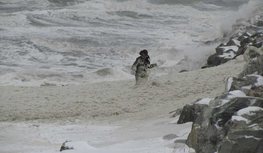 Charlie Weyauvanna plays in sea foam late on Tuesday, Nov. 8, 2011, as a large Bering Sea storm intensifies in Nome, Alaska. (AP Photo/Anchorage Daily News, Peggy Fagerstrom)