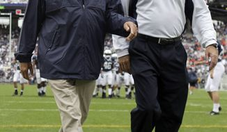 ** FILE ** Penn State coach Joe Paterno (left) walks with assistant coach Tom Bradley on the field before an NCAA college football game against Syracuse in State College, Pa., on Sept. 12, 2009. The university's trustees have chosen Bradley as interim head coach for the remainder of the season. (AP Photo/Carolyn Kaster, File)