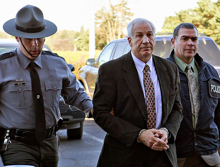 """Former Penn State football defensive coordinator Gerald """"Jerry"""" Sandusky (center) arrives in handcuffs at the office of Centre County Magisterial District Judge Leslie A. Dutchcot while being escorted by Pennsylvania state police and state attorney general's office officials on Saturday, Nov. 5, 2011, in State College, Pa. Sandusky is charged with sexually abusing eight young men. (AP Photo/The Patriot-News, Andy Colwell)"""