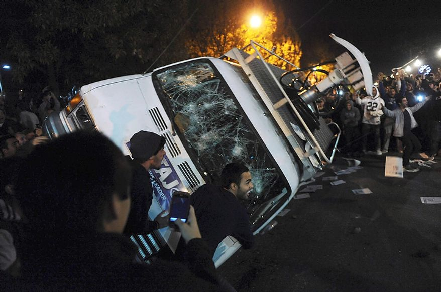 Penn State students flip a television news van during a riot after it was announced on Wednesday, Nov. 9, 2011, that Joe Paterno no longer would be head football coach. (AP Photo/Pittsburgh Post-Gazette, Michael Henninger)