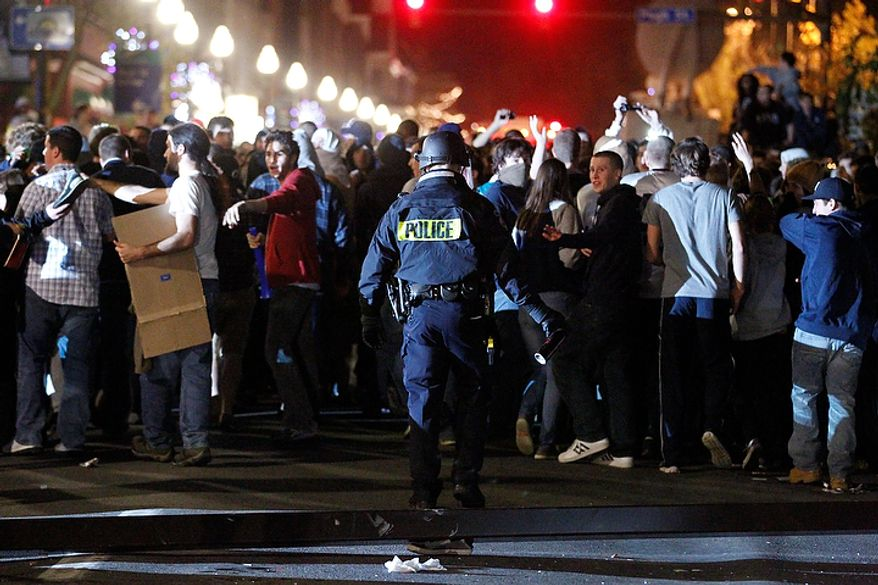 "Police hold back Penn State students after they reacted off campus early on Thursday, Nov. 10, 2011, in State College, Pa., to the firing of football coach Joe Paterno on Wednesday. Hundreds of students gathered about two blocks from the campus, with some chanting, ""We want Joe! We want Joe!"" Some shook a lamppost, and others tipped over a news van, kicking out its windows. Police fired bursts of pepper gas. (AP Photo/Matt Rourke)"