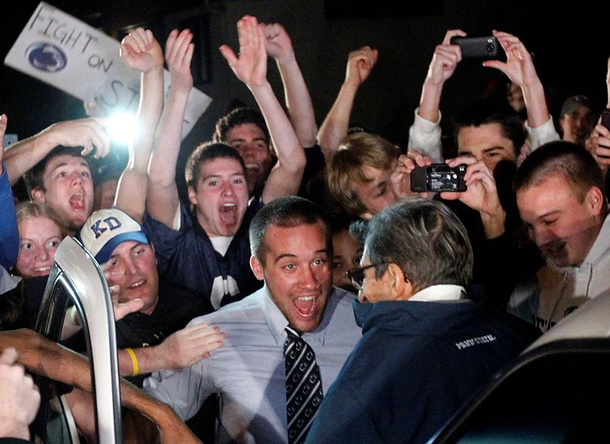 """Students greet Penn State coach Joe Paterno as he arrives at his home on Tuesday, Nov. 8, 2011, in State College, Pa. Paterno's support among the Penn State board of trustees was described Tuesday as """"eroding,"""" threatening to end the 84-year-old coach's career amid a child-sex-abuse scandal involving a former assistant and one-time heir apparent. (AP Photo/Matt Rourke)"""