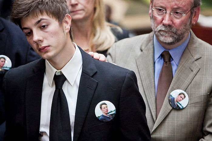 Jimmy Hoover, 19, left, younger brother of John Hoover, a victim killed in crash by Kevin Coffay, is comforted by a family member while listening as John McCarthy, Montgomery County state's attorney, speaks to the press after Coffay, 20, pled guilty in Montgomery County Circuit Court on three counts of vehicular manslaughter and one count of leaving the scene of a fatal crash, in Rockville, Md. on Nov. 10, 2011. Hoover wears a pin with a photograph of his brother.