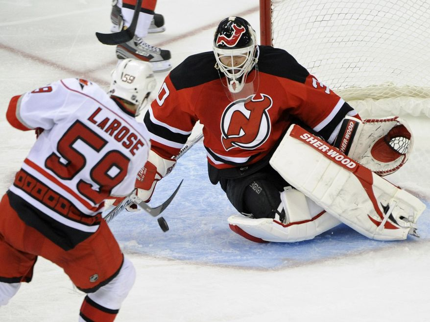 New Jersey Devils goaltender Martin Brodeur, right, makes a save on a shot by Carolina Hurricanes' Chad LaRose during the second period of an NHL hockey game Tuesday, Nov. 8, 2011, in Newark, N.J. (AP Photo/Bill Kostroun)