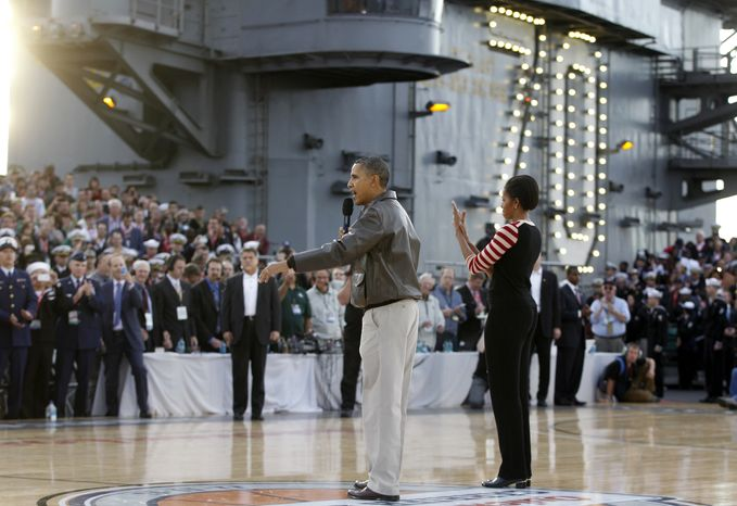 President Barack Obama speaks to the crowd as first lady Michelle Obama listens before the Carrier Classic NCAA college basketball game between Michigan State and North Carolina aboard the USS Carl Vinson, Friday, Nov. 11, 2011, in Coronado, Calif. (AP Photo/Charles Dha