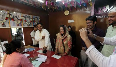 Mohammed Zaffar Patel, standing second left, weds Jannat Khan, third left, at a marriage registrar's office in Mumbai, India, Friday, Nov. 11, 2011. Because of the days numerical conjunction, 11.11.11, people believe it to be an auspicious day leading thousands of couples to tie their knots on this day across India. (AP Photo/Rajanish Kakade)