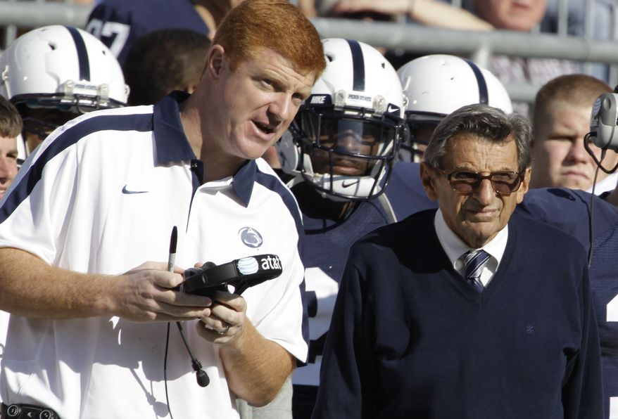 ** FILE ** In this Oct. 8, 2011, file photo, Penn State assistant football coach Mike McQueary, left, talks with head coach Joe Paterno during an NCAA college football game against Iowa, in State College, Pa. (AP Photo/Gene Puskar, File)
