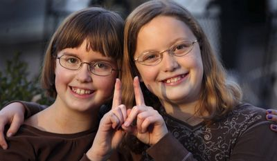 In a Monday, Nov. 7, 2011, photo, twin sisters Betsy, left, and Katie Overman pose for a photo in Madison, Wisc. The twins turned 11 on Nov. 11, 2011, or 11/11/11. (AP Photo/Wisconsin State Journal, Craig Schreiner)