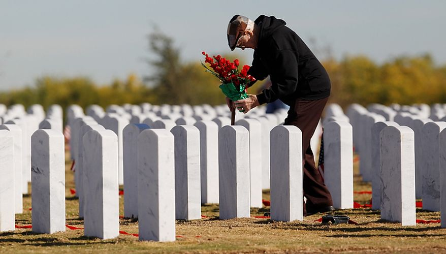 Flowers are placed at a grave site by an unidentified man during a Veteran's Day observance at Fort Sam Houston National Cemetery, Friday, Nov. 11, 2011, in San Antonio. (AP Photo/Eric Gay)
