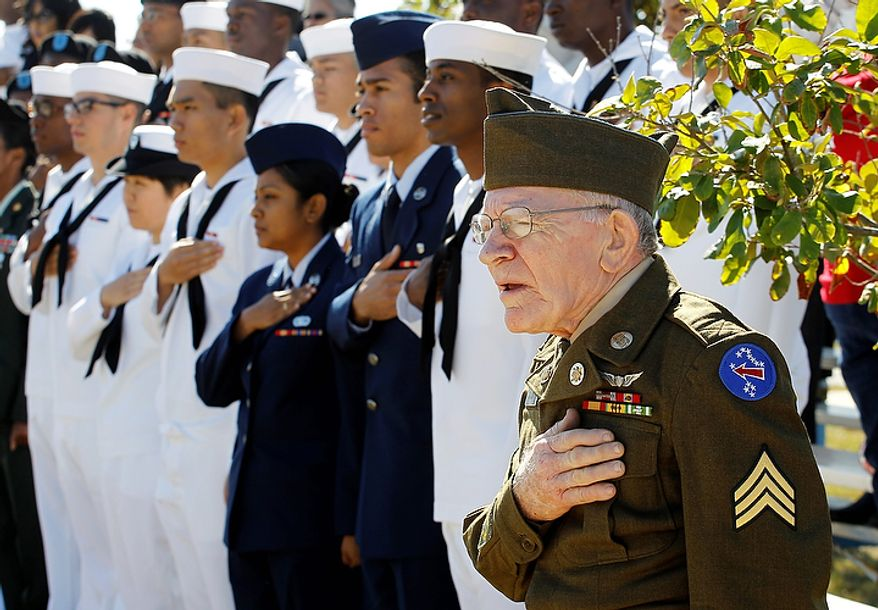 Korean War veteran James Gerard, right, wearing his original uniform, salutes during a Veteran's Day observance at Fort Sam Houston National Cemetery, Friday, Nov. 11, 2011, in San Antonio. (AP Photo/Eric Gay)